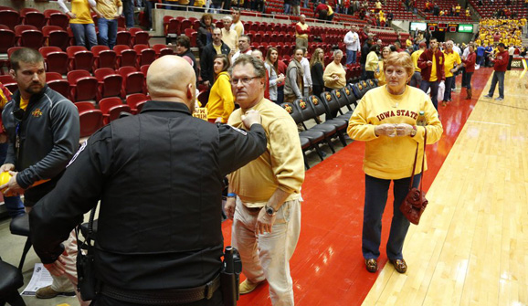 An Iowa State fan upset at the ending of a game against Kansas is restrained by police.