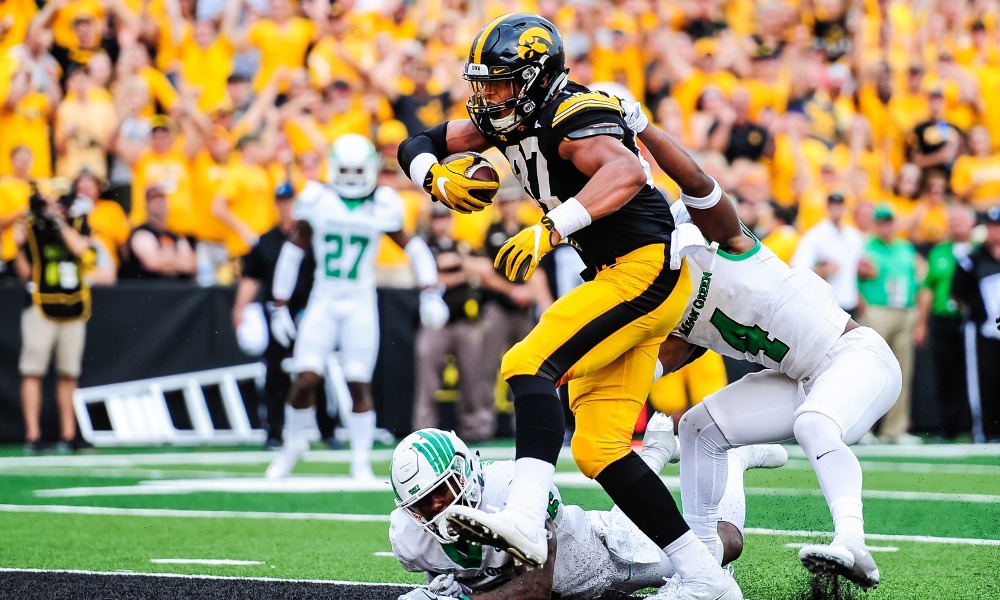 Sep 16, 2017; Iowa City, IA, USA; Iowa Hawkeyes tight end Noah Fant (87) scores a touchdown as North Texas Mean Green safety Keshawn McClain (6) and safety Khairi Muhammad (4) attempt to tackle during the third quarter at Kinnick Stadium. Mandatory Credit: Jeffrey Becker-USA TODAY Sports