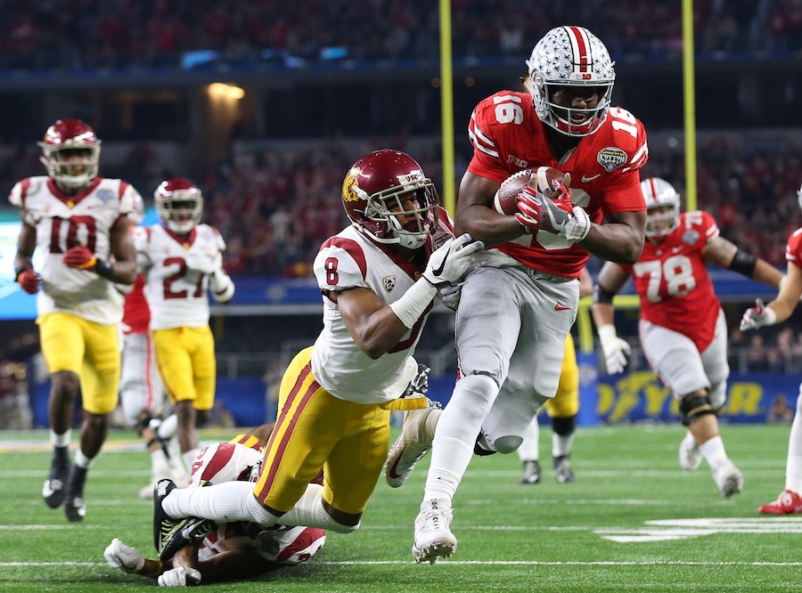 December 29, 2017; Arlington, TX, USA; Ohio State Buckeyes quarterback JT Barrett (16) is aiming for a touchdown in the second quarter against cornerback Iman Marshall (8) of the Southern California Trojans at the Cotton Bowl AT & AT Stadium. T. Mandatory Credit: Matthew Emmons-USA TODAY Sports