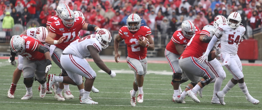 J.K. Dobbins running through a hole opened by his offensive line
