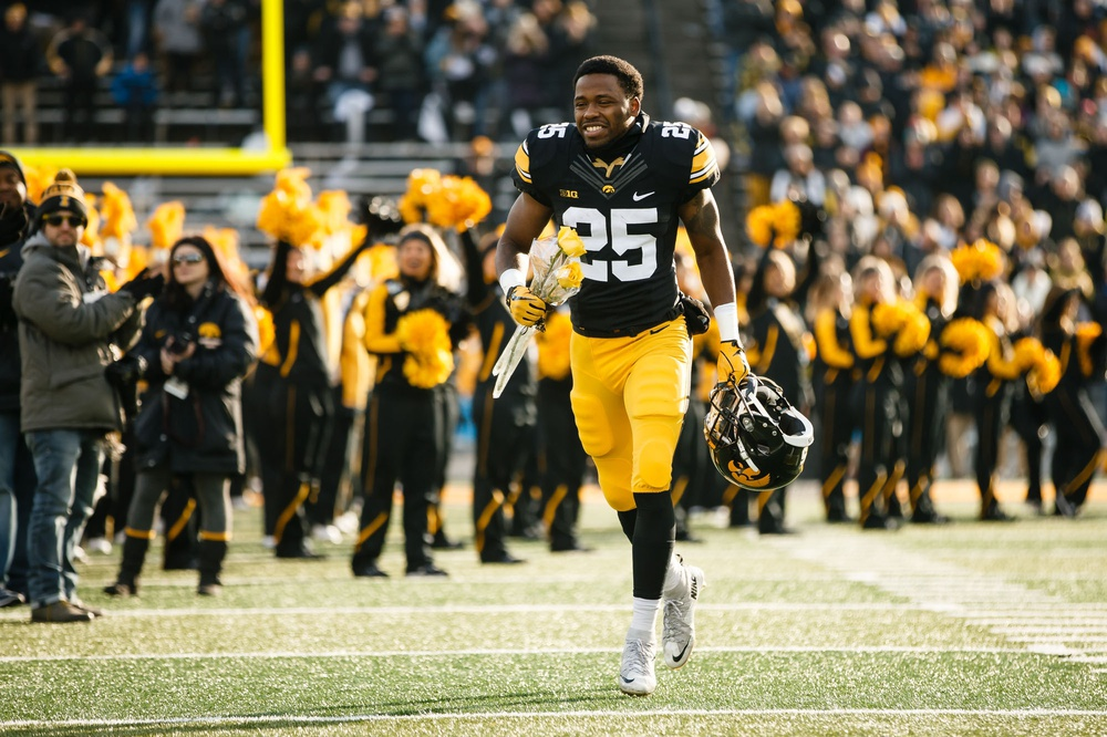 Nov 18, 2017; Iowa City, IA, USA; Iowa player Akrum Wadley (25) runs to greet his parents for senior day before playing Purdue at Kinnick Stadium. Mandatory Credit: Brian Powers/The Des Moines Register via USA TODAY Sports