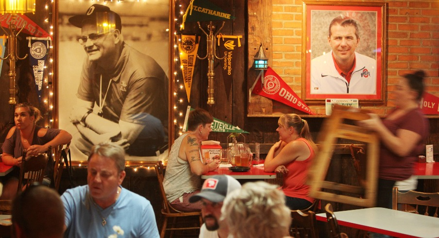Servers and diners mingle beneath portraits of Woody Hayes and Urban Meyer at Plank's Cafe, 743 Parsons Ave.