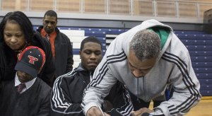Greg McDowell, father of Michigan State football commit Malik McDowell, signs paperwork at his son's national signing day press conference at Southfield High School on Wednesday. It's not known what documents were signed, but the Spartans have yet to receive a signed national letter of intent or Big Ten tender document. (Katie Bailey l MLive.com)