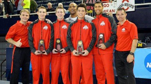 Men's gymnastics team with trophies