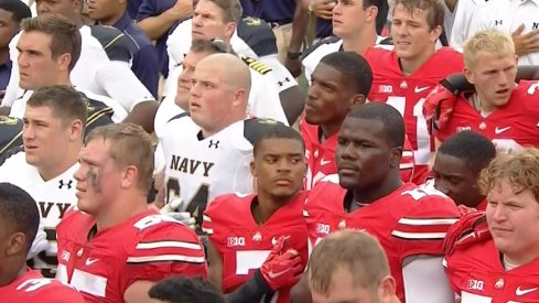 Ohio State and Navy football players gather for the schools' alma maters following the game.