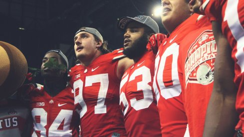 Joey Bosa and Michael Bennett sing Carmen Ohio with teammates following the Big Ten Championship game.