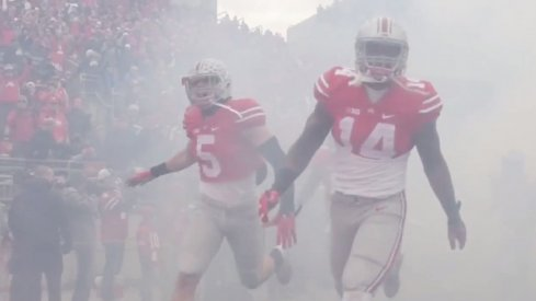 Jeff Heuerman and Curtis Grant bust through the smoke to run onto the Ohio Stadium field.