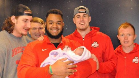 Ohio State All-American defensive tackle Michael Bennett holds a three-week-old baby, Bayah, at Nationwide Chilrden's Hospital Friday.