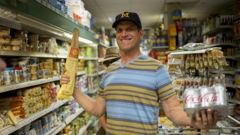Jim Harbaugh in France, showing off some groceries.