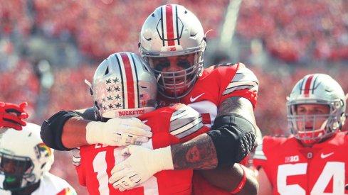 Taylor Decker hugs Ezekiel Elliott after a touchdown run against Hawai'i