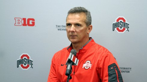 Urban Meyer stands at the podium.