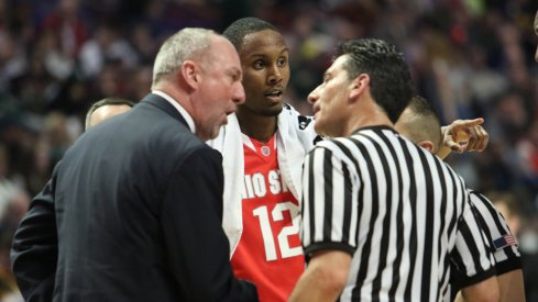 Thad Matta talks with an official.