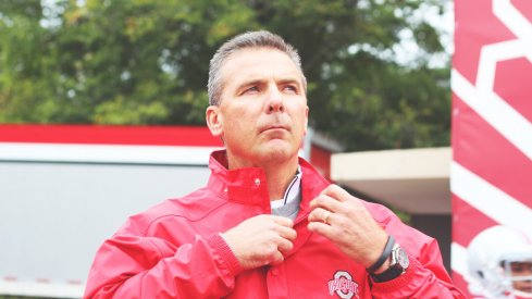 Urban Meyer stands in the rain.