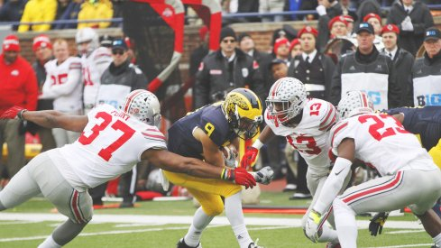 Joshua Perry, Eli Apple and Tyvis Powell combine to make a tackle vs. Michigan.