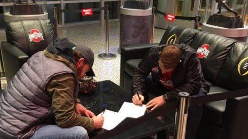 Craig Fada and Joe Burger sign their scholarship deals.