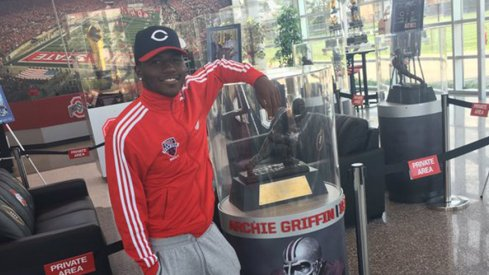 Five-star wide receiver Tyjon Lindsey poses with Archie Griffin's Heisman Trophy at the Woody Hayes Athletic Center