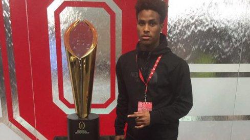 Kareem Felder poses next to Ohio State's national championship trophy