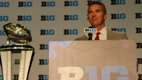 Urban Meyer and the B1G championship trophy.