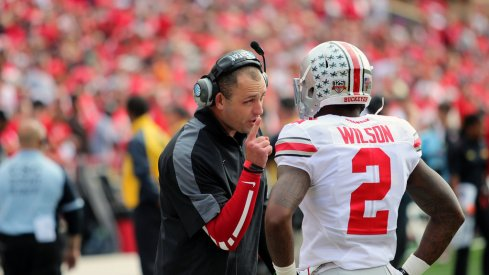 Zach Smith speaks with Dontre Wilson on the sideline.