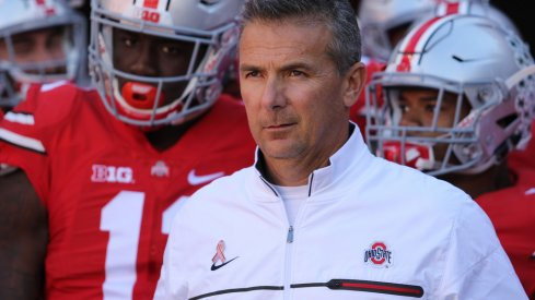 Urban Meyer leads his team on the field against Indiana.
