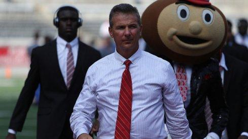 Urban Meyer rolls into Ohio Stadium with Brutus Buckeye.