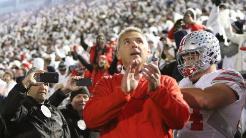 Urban Meyer leads his team out onto the field at Penn State.