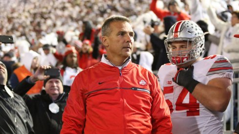 Urban Meyer guides his team onto the field.