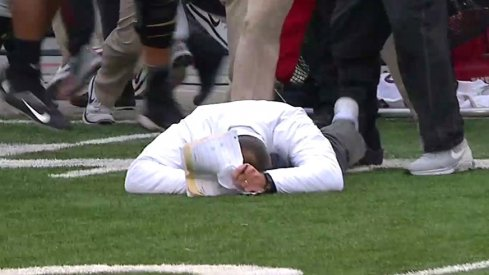 Urban Meyer lies on the ground motionless after his Buckeyes topped No. 3 Michigan in double overtime