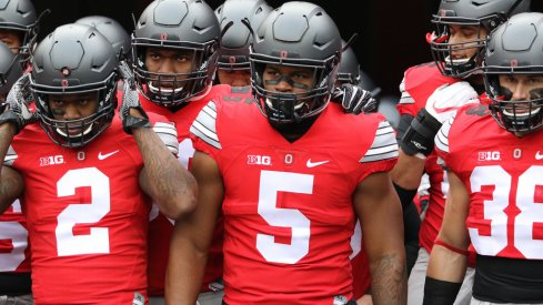 Dontre Wilson and Raekwon McMillan lead Ohio State onto the field.