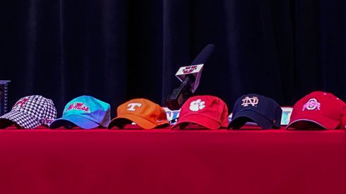 Hats sit on a table prior to five-star offensive tackle Trey Smith's announcement