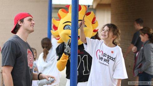 Drue Chrisman helps paint a pole at Alta E. Butler Elementary School in Phoenix