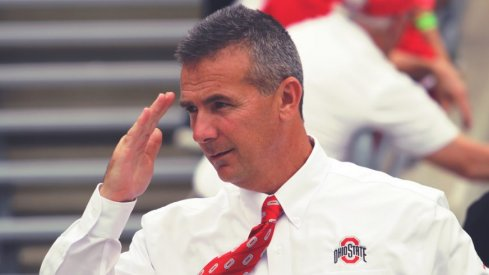 Urban Meyer salutes before a game.