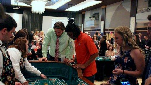 Nick Bosa and Damon Arnette play craps at ATO casino night.