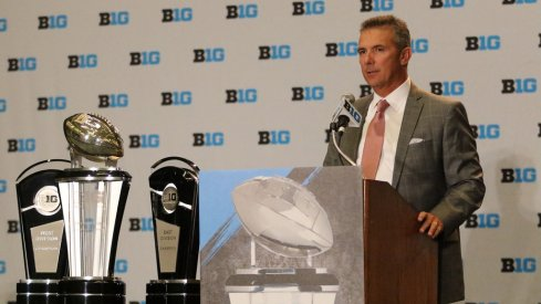 Ohio State coach Urban Meyer and the Big Ten trophies.