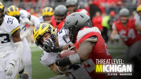 Ohio State running back Mike Weber stiffarms a Michigan Wolverine