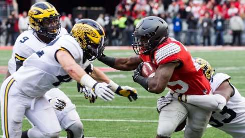 Nov 26, 2016; Columbus, OH, USA; Ohio State Buckeyes running back Mike Weber (25) tries to get past Michigan Wolverines defensive end Taco Charlton (33) and linebacker Ben Gedeon (42) at Ohio Stadium. Ohio State won the game 30-27 in double overtime.