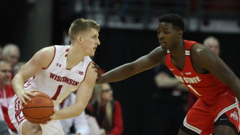 Ohio State basketball player Jae'Sean Tate guards a Wisconsin player