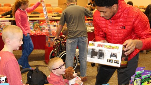 Malik Harrison helps a child pick out a toy during the Buckeyes' visit to the Nationwide Children's Hospital on Monday.