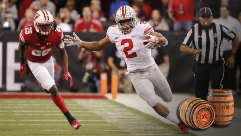 Dec 2, 2017; Indianapolis, IN, USA; Ohio State Buckeyes running back J.K. Dobbins (2) attempts to stay in bounds as he is chased by Wisconsin Badgers cornerback Derrick Tindal (25) in the third quarter in the Big Ten championship game at Lucas Oil Stadium. Mandatory Credit: Mark Hoffman/Milwaukee Journal Sentinel via USA TODAY Sports