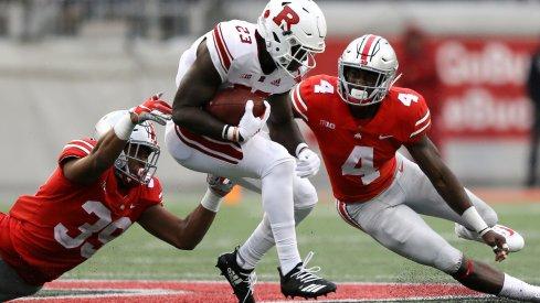 Jordan Fuller and Malik Harrison combine for a tackle against a Rutgers ballcarrier.
