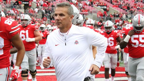 Urban Meyer runs out onto the field in his first game back from suspension.