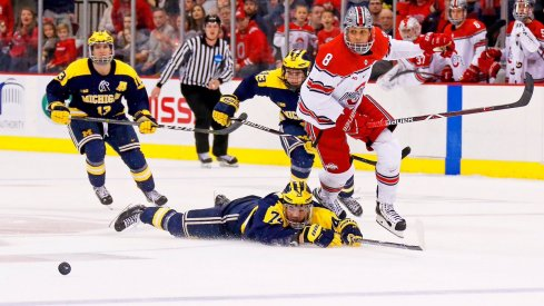 Buckeye forward Dakota Joshua speeds after the puck while the Michigan Wolverines look on.