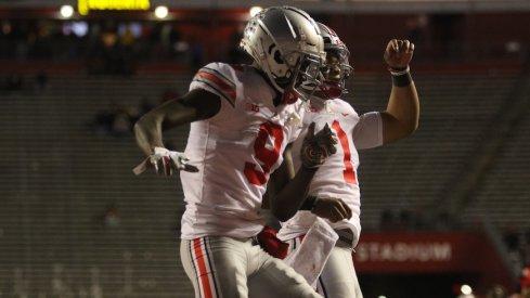 Justin Fields and Binjimen Victor celebrate a touchdown.