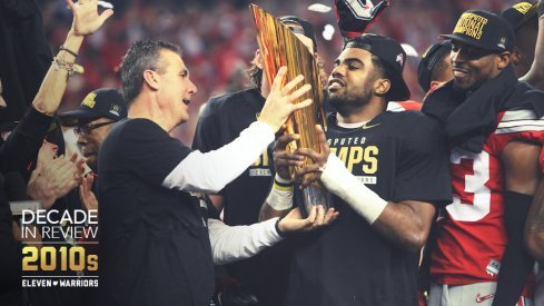Urban Meyer hands the national championship trophy for the 2014 season to Ezekiel Elliott.