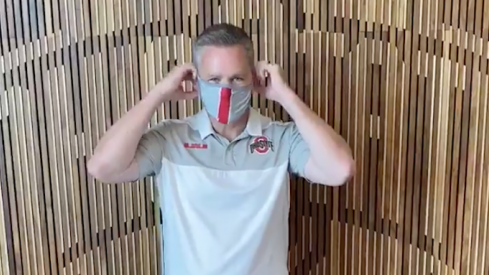 Chris Holtmann puts on a mask.