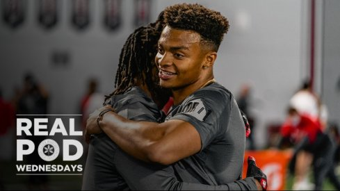 Justin Fields smiles and hugs Trey Sermon after his pro day workout.