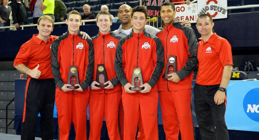 Men's gymnastics team with trophies