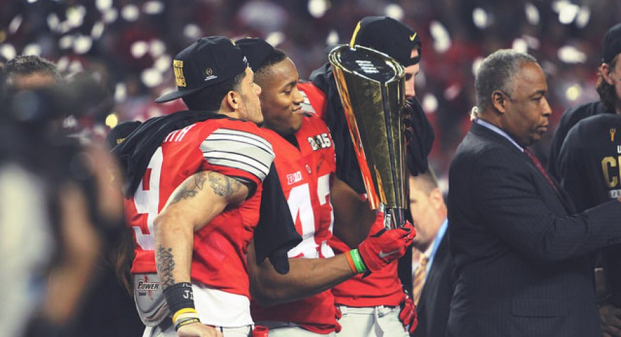 Devin Smith (left) and Darron Lee (right) spend time with the CFP trophy.