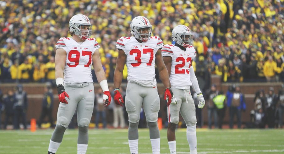 Joey Bosa, Joshua Perry and Tyvis Powell on the field against Michigan.