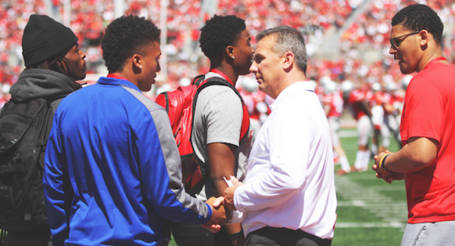 Urban Meyer surrounded by Buckeye recruits.